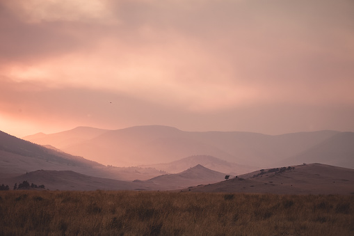 A Montana landscape scenic. Smoke from a nearby forest fire creating a very hazy sky and dreamy ethereal light. No people, horizontal composition and copy space.