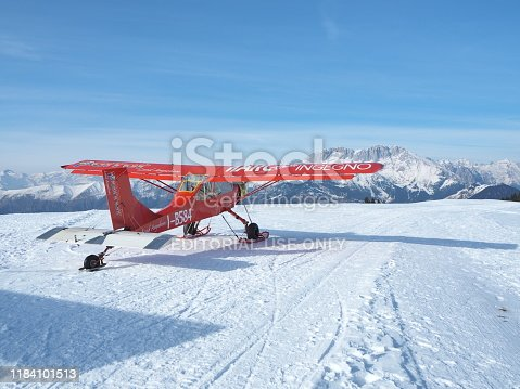 Monte Pora, Bergamo, Italy. A single engined, general aviation red light aircraft parked on a snow covered plateau. Italian Alps