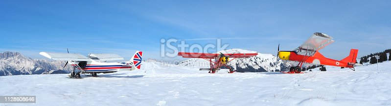 Monte Pora, Bergamo, Italy. A single engined, light aircrafts parked on a snow covered plateau. Red and UK flag colors as livery. Planes parked in a free outdoor area near the ski slopes and trails