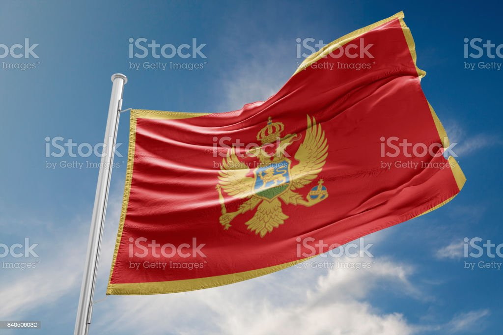 Montenegro Flag is Waving Against Blue Sky stock photo