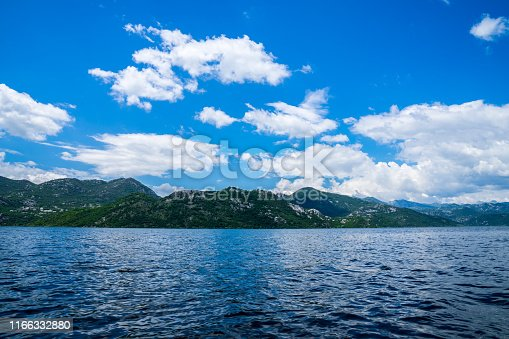 Montenegro, Green mountains alongside coast of lakeside of skadar lake waters viewed from boat in national park