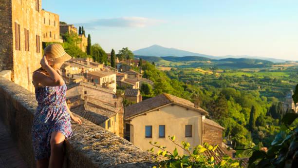 montepulciano, toskana, italien, mädchen schaut die landschaft der stadt und landschaft vom balkon - toskana ferien stock-fotos und bilder