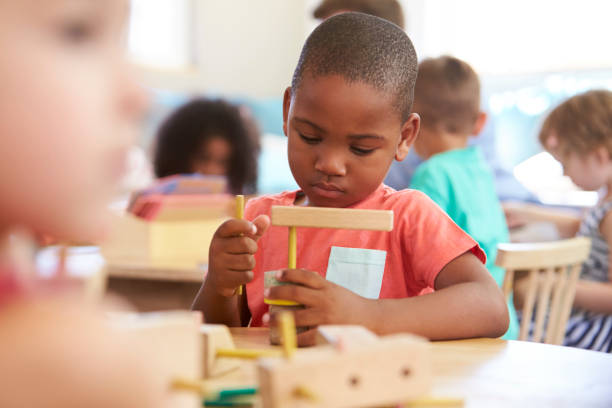 Montessori Pupil Working At Desk With Wooden Shapes Montessori Pupil Working At Desk With Wooden Shapes 2 3 years stock pictures, royalty-free photos & images