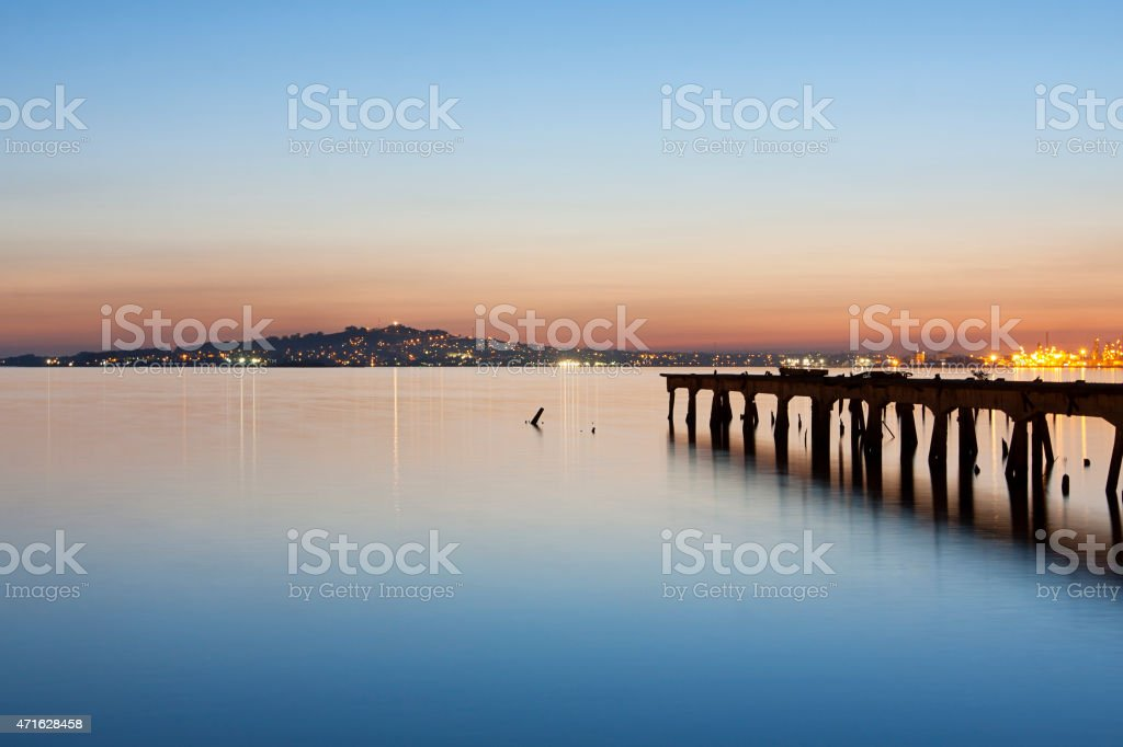 Montevideo cityscape harbor bay at dusk with pier stock photo