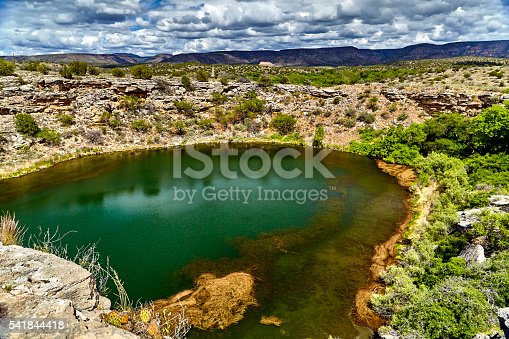 Natural sink hole in limestone in the American southwest used by the ancient Sinagua with cliff dwellings in the side of the cliff surrounding the water