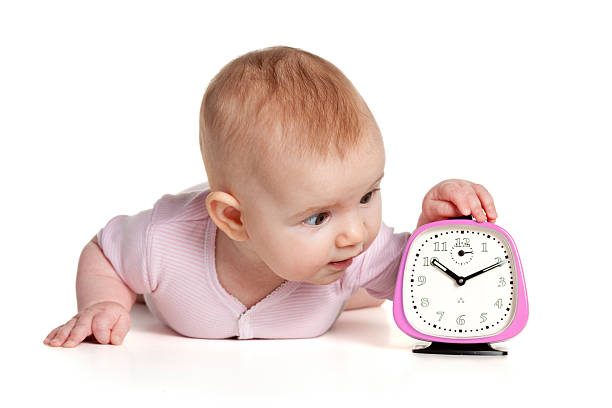 4 month baby girl with retro alarm clock stock photo