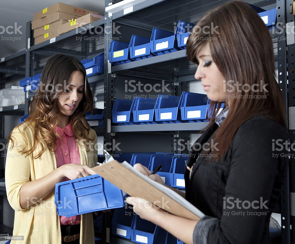 Month end inventory count in a stockroom Two young women counting inventory in a stockroom 20-24 Years Stock Photo