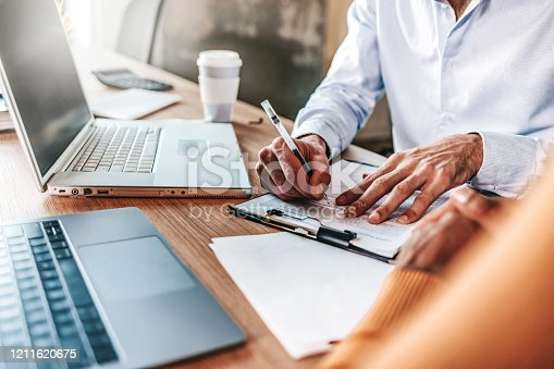 Couple reading legal documents at home with laptop, family considering mortgage loan or insurance, studying contract details, discussing terms and conditions, close up view of hands holding papers.