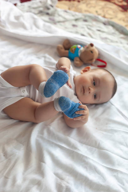 6-8 month old baby boy lying playfully in bed stock photo