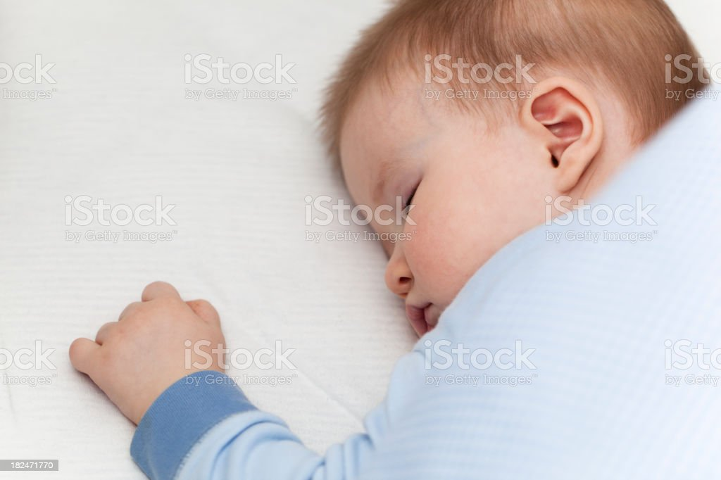 8 month old baby boy sleeping peacefully in his bed. royalty-free stock photo