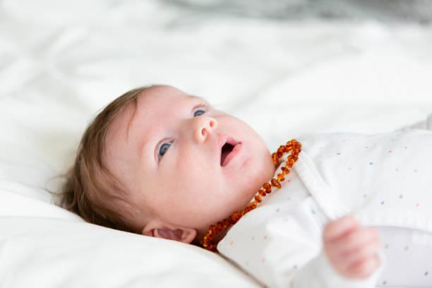 3 Monate alte schöne, niedliche Baby mit Bernsteinkette – Foto