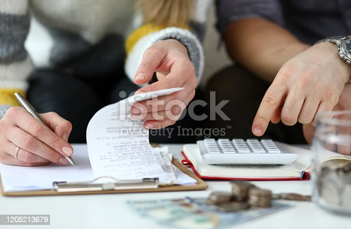 Close-up view of man and woman making account of family income. Writing down and calculating expenses. Attentive review of finance. Calculator on desk. Economy concept
