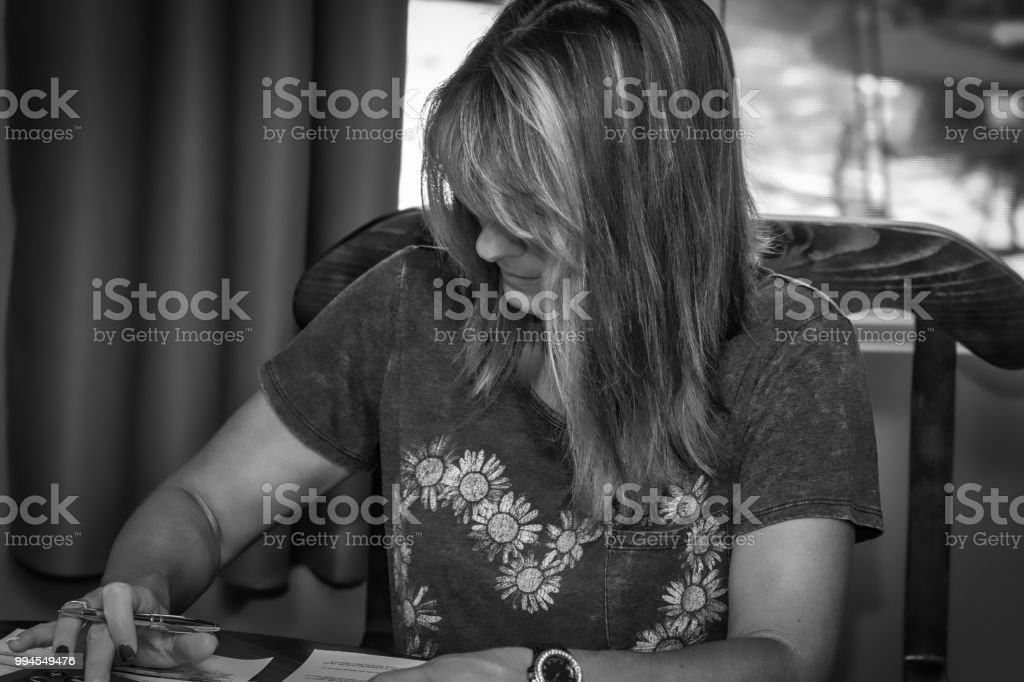 A mature woman works in her home office for business in casual...