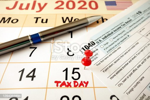 1170746979 istock photo Monthly calendar showing date July 15th 2020 marked as tax day with 1040 form and pen 1254055894