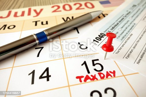 1170746979 istock photo Monthly calendar showing date July 15th 2020 marked as tax day with 1040 form and pen 1254416657