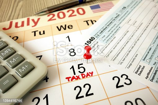 1170746979 istock photo Monthly calendar showing date July 15th 2020 marked as tax day with 1040 form calculator and pen 1254416744