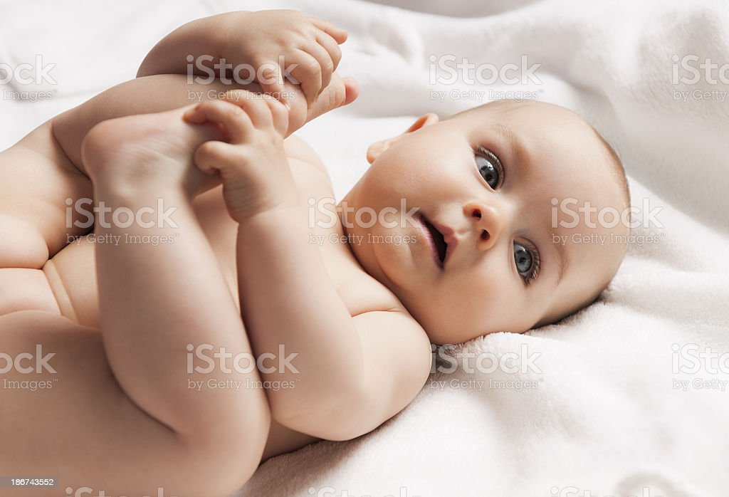 6-7 months old baby child playing with feet, lying down stock photo
