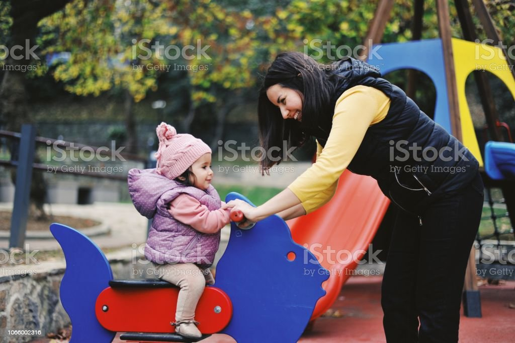 11 months old baby girl playing with her mom at a park stock photo