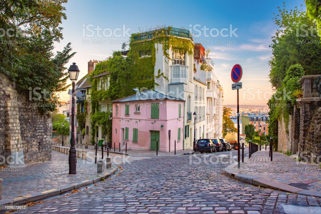 Montmartre in Paris, France Cozy old street with pink house at the sunny sunrise, quarter Montmartre in Paris, France Ancient Stock Photo