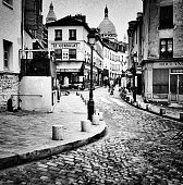 Paris, France - May 9, 2015: These are black and white, monochrome images of the Montmartre district of Paris. This is known as the artist area of Paris and is a famous tourist destination. It is an overcast afternoon in Spring, March. This is a corner with cobbled streets and old buildings. There are people in the distance.