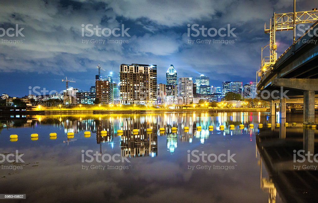 Montreal skyline at night with bridge and water reflections stock photo
