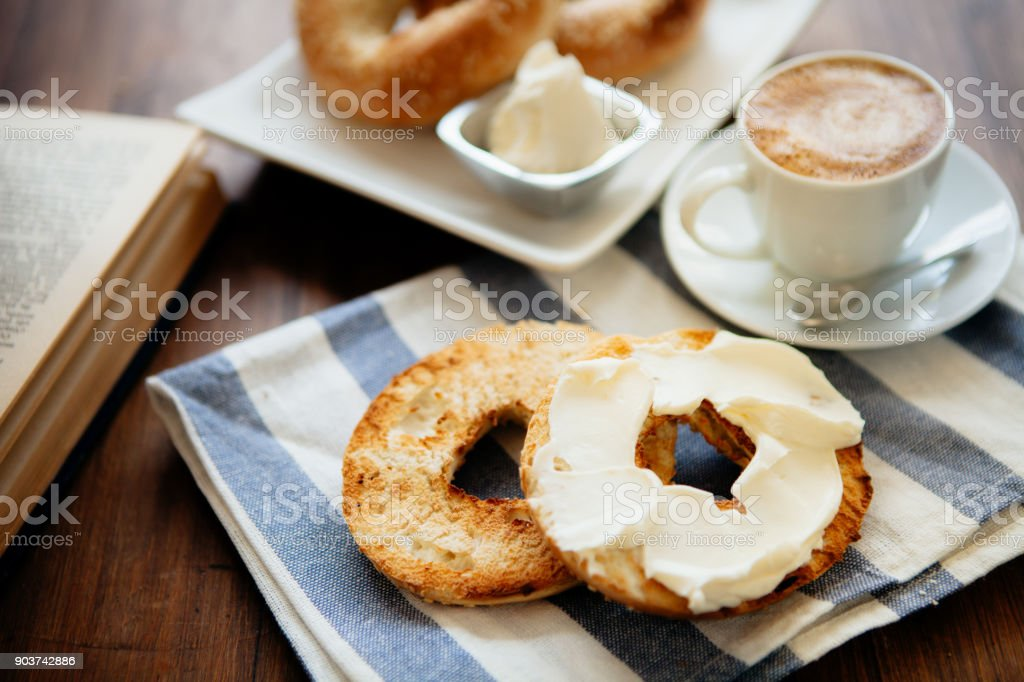 Montreal style bagels on a plate with cream cheese and coffee