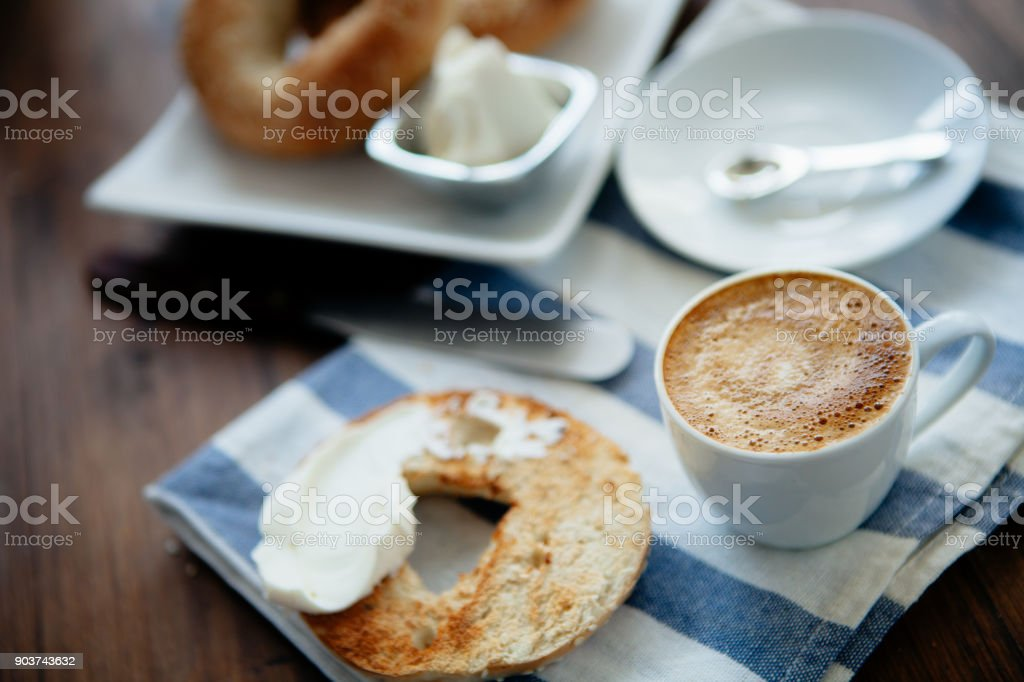 Montreal style bagels on a plate with cream cheese and coffee stock photo