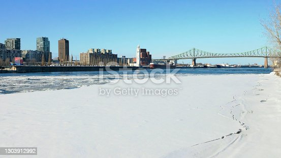 Montreal's Pont Jacques-Cartier wide view on a clear Winter day with the iced and snow covered Saint-Lawrence river underneath.