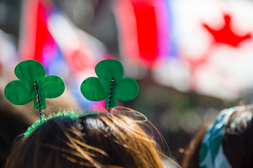 Montreal, Canada - 19 March 2017: a spectator wearing clover shaped head boppers is looking at St. Patrick's parade
