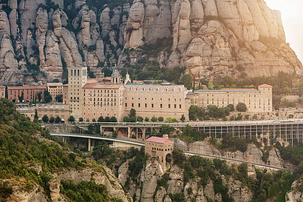Montserrat Monastery Barcelona Catalonia Spain Sunset at Santa Maria de Montserrat Monastery. Famous Benedictine Monastery in between cliffs in the mountains near Barcelona, in Catalonia, Spain abbey monastery stock pictures, royalty-free photos & images
