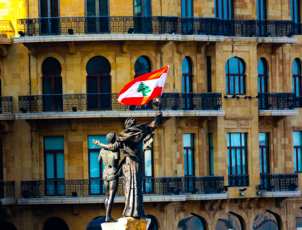 monument at martyrs square in beirut with lebanese flag - beirut стоковые фото и изображения