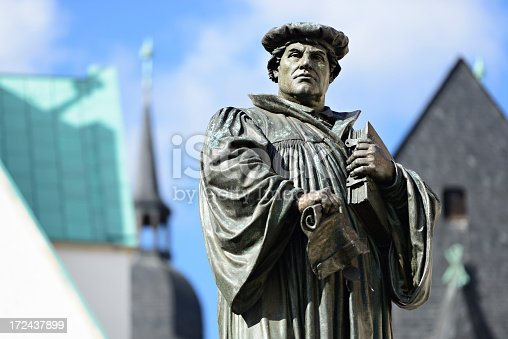 Monument of Martin Luther in Eisleben, the town of his birth and death, medieval architecture in the background