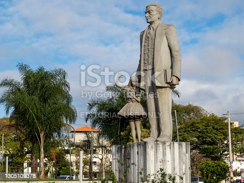 istock Monument to Monteiro Lobato at the entrance to the city of Taubate, against the blue sky with clouds. 1305109378