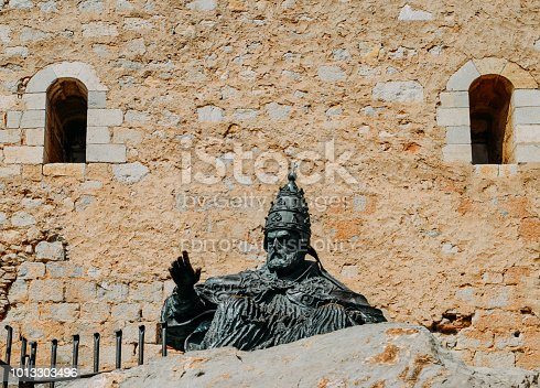 Peniscola, Spain - July 12, 2018: Monument to Papa Luna, in Peniscola Castle, in Valencia Spain. This imposing bronze statue sits at the foot of the castle. From 1415 to 1423 it was the home of the schismatic Avignon pope Benedict XIII (Pedro de Luna), whose name is commemorated in the Castell del Papa Luna, the name of the medieval castle, and Bufador del Papa Luna, a curious cavern with a landward entrance through which the seawater escapes in clouds of spray.