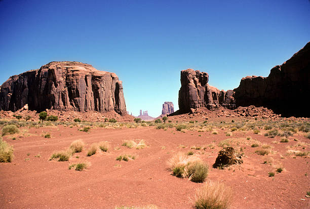 Monument Valley 1986 Red rock and shrubs in foreground with the majestic formations of Monument Valley in the distance. hearkencreative stock pictures, royalty-free photos & images