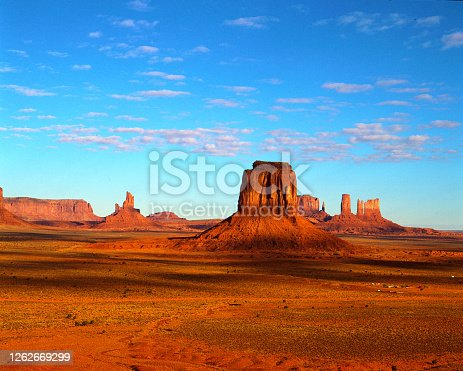 Monument Valley  at sunset with vast sandstone and buttes rising above the valley floor on the Arizona-Utah state line