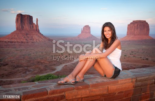 Beautiful woman enjoying the view over Monument Valley on this wonderful day at sunset. Nikon D3X. Converted from RAW. Polarizer.
