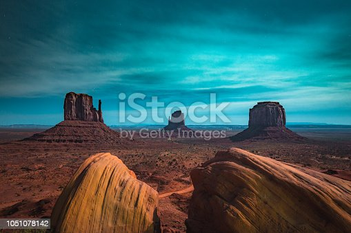 Classic panoramic view of scenic Monument Valley with the famous Mittens and Merrick Butte illuminated in beautiful mystic moonlight on a starry night in summer, Arizona, American Southwest, USA