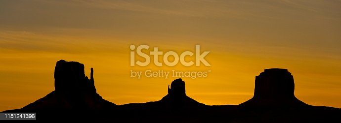 Monument Valley is on the Arizona/Utah border near Oljato, Utah, USA. The valley with its strange sandstone formations is the epitome of the Old West. This iconic view was taken at sunset, capturing a silhouette of the rock formations.