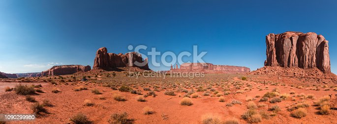 Monument Valley, a red-sand desert region on the Arizona-Utah border, is known for the towering sandstone buttes of Monument Valley Navajo Tribal Park. Monument valley landscape with buttes.