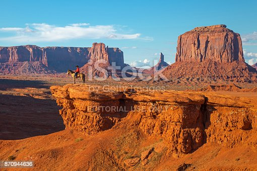 The John Ford's viewpoint inside the Monument Valley Navajo Tribal Park with a Navajo Horseman staging the scene of the movie Stagecoach at sunset, Arizona, USA.