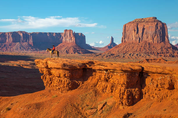 Monument Valley Navajo Horseman The John Ford's viewpoint inside the Monument Valley Navajo Tribal Park with a Navajo Horseman staging the scene of the movie Stagecoach at sunset, Arizona, USA. navajo sandstone formations stock pictures, royalty-free photos & images
