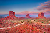 Beautiful dramatic sunset over the East, West Mitten Butte and Merrick Butte in Monument Valley. Utah, USA