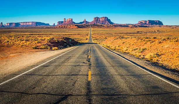 Monument Valley straight desert road through iconic Western landscape Utah stock photo