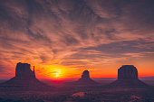 The sun rises between the West and East Mittens in Monument Valley on the border of Arizona and Utah.