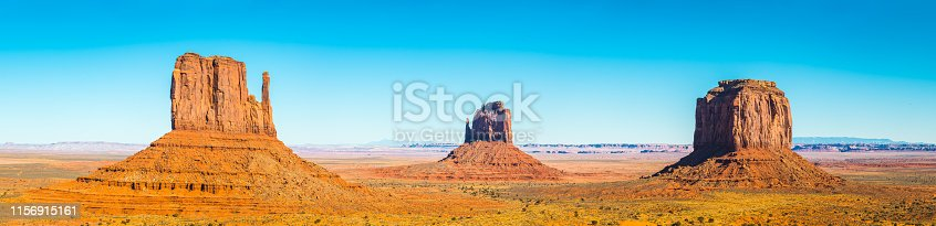 Panoramic view across the sandy desert of southern Utah to the iconic Mitten buttes of Monument Valley, the dramatic sandstone landscape in the heart of the Navajo Nation Reservation, USA.