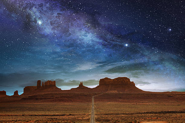 monument valley under a night starry sky stock photo