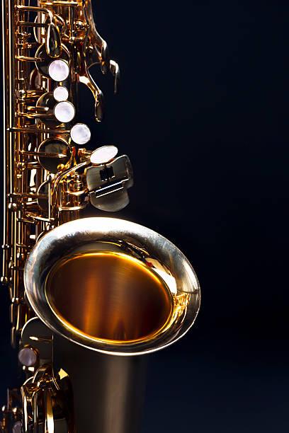 stimmungsvolle blautöne: saxophon mit dunkelblauem textfreiraum - altsaxophon stock-fotos und bilder