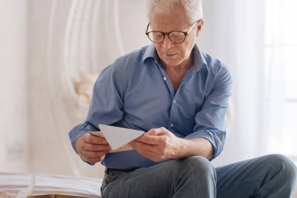 mal humor sombrío hombre leyendo una carta antigua - postal worker fotografías e imágenes de stock