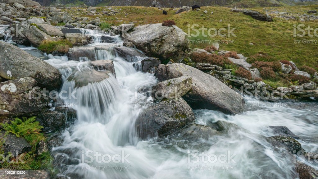 Moody landscape image of river flowing down mountain range near Llyn Ogwen and Llyn Idwal in Snowdonia in Autumn stock photo